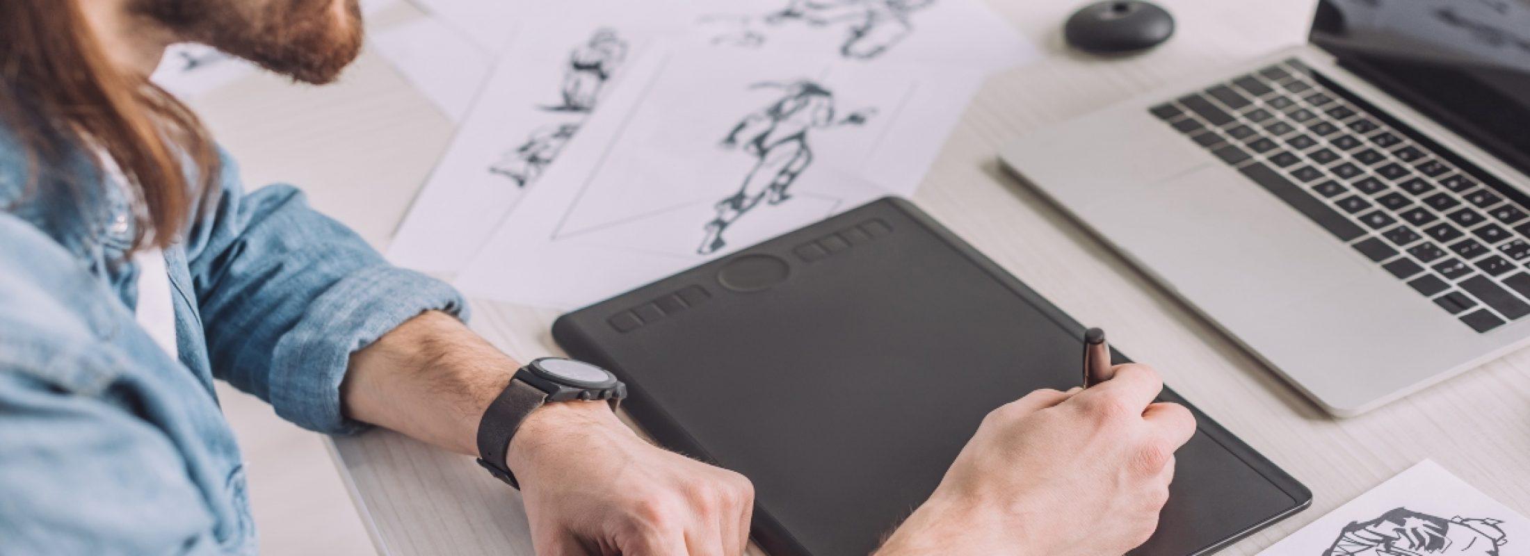 cropped view of animator in headphones using digital tablet